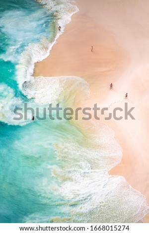 View from above, stunning aerial view of some people relaxing on a beautiful beach bathed by a turquoise sea during sunset. Kelingking beach, Nusa Penida, Indonesia. Royalty-Free Stock Photo #1668015274