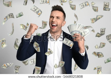 Happy young man with dollars under money rain on light background Royalty-Free Stock Photo #1668021808