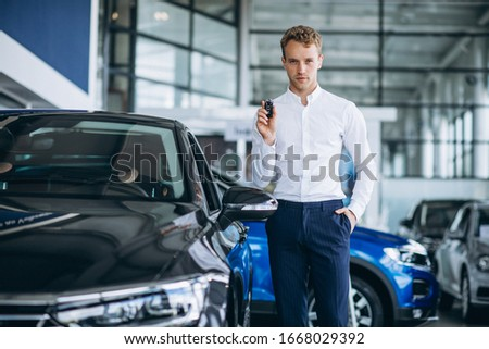 Young handsome man choosing a car in a car showroom #1668029392