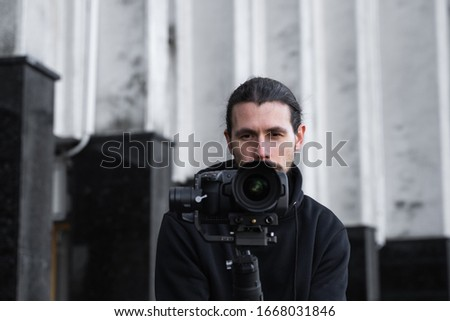 Young Professional videographer holding professional camera on 3-axis gimbal stabilizer. Pro equipment helps to make high quality video without shaking. Cameraman wearing black hoodie making a videos. #1668031846