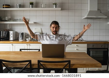 Excited businessman feeling happy about successful project. Man holding hands in the air and looking at laptop while sitting on a kitchen at home. Happy freelancer, student working at laptop at home. #1668031891