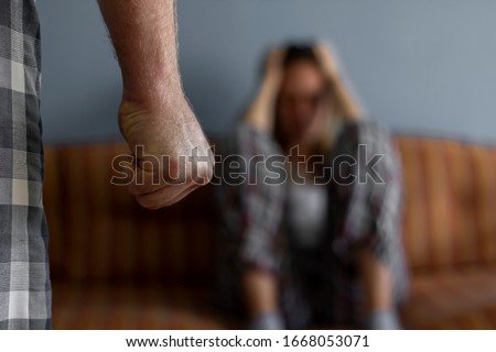 Photo of young woman sitting on sofa at home,focus is on man's fist in the foreground of the image.Home violence concept.Frightened woman and men's fist.Woman is victim of domestic violence and abuse. #1668053071