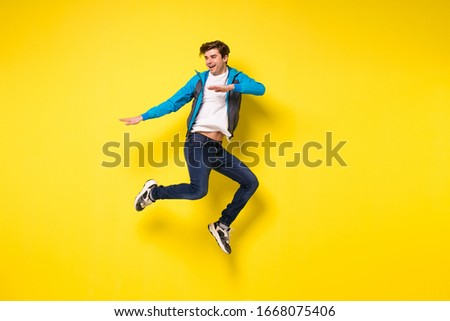 Mid-air shot of handsome young man jumping and gesturing, showing excitment #1668075406