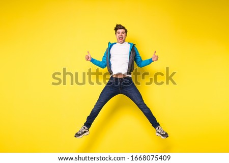 Mid-air shot of handsome young man jumping and gesturing, showing excitment #1668075409