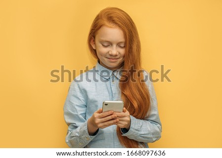adorable smiling caucasian red haired girl with mobile phone, pretty kid girl using smartphone, enjoy chatting with friend. isolated yellow background.