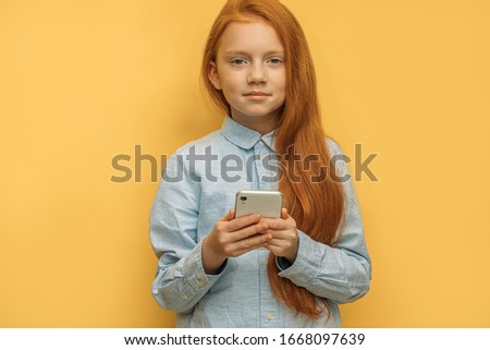 sweet caucasian red haired kid girl with in hands, beautiful girl use mobile phone, modern technologies, watch videos and chat with friends. yellow background