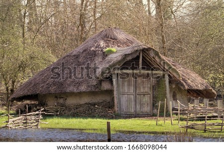 Reconstruction Of A Bronze Age Roundhouse With Thatched Roof And Doors Closed On The Edge Of A Flooded Marsh. Taken at Testwood Lakes, UK, Where Two Of The Oldest Bridges Were Found In Britain. Royalty-Free Stock Photo #1668098044