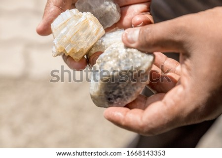 Man's hands with picked raw moonstones from rocks on Sri-Lanka mine. #1668143353