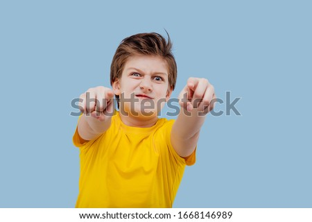 Angry male teenager in yellow t shirt looking at camera and showing with fingers at camera on yellow background #1668146989