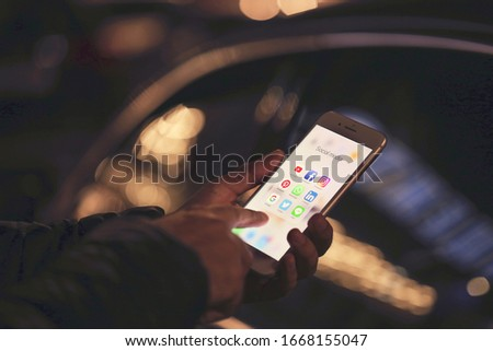 MYKOLAIV, UKRAINE - OCTOBER 19, 2019: Man holding and using mobile phone with icons of social media on night time #1668155047