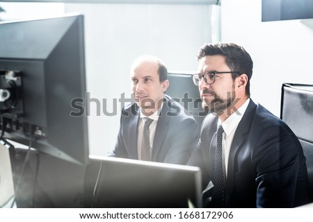 Image of two thoughtful businessmen looking at data on multiple computer screens, solving business issue at business meeting in modern corporate office. Business success concept. #1668172906
