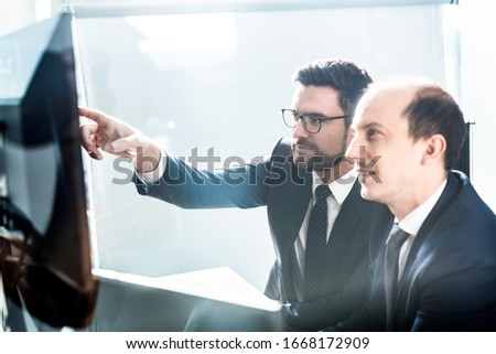 Image of two thoughtful businessmen looking at data on multiple computer screens, solving business issue at business meeting in modern corporate office. Business success concept. #1668172909