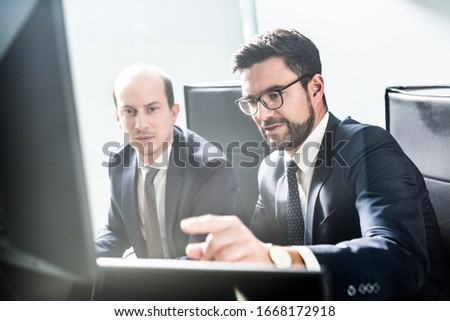 Image of two thoughtful businessmen looking at data on multiple computer screens, solving business issue at business meeting in modern corporate office. Business success concept. #1668172918