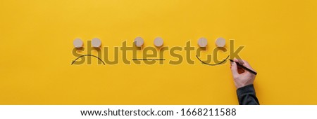 Customer feedback and satisfaction conceptual image - male hand drawing happy, sad and neutral faces over yellow background. Royalty-Free Stock Photo #1668211588