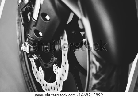 The front tire of a parked custom motorcycle Royalty-Free Stock Photo #1668215899