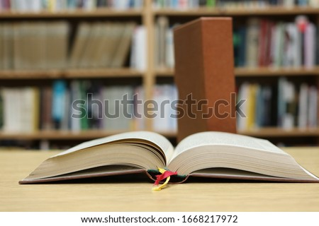 Open book on the table in library  #1668217972