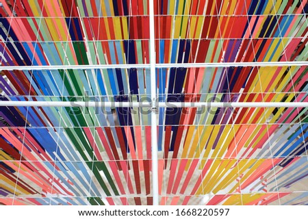 Multi-colored ribbons hanging from the ceiling. Bright and colorful background,party and congratulations. The background is bright like a rainbow. #1668220597