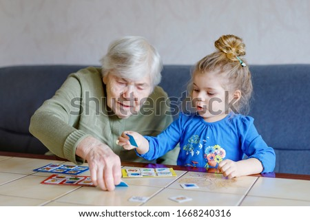 Beautiful toddler girl and grand grandmother playing together pictures lotto table cards game at home. Cute child and senior woman having fun together. Happy family indoors