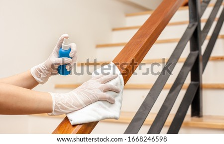 Deep cleaning for Covid-19 disease prevention. alcohol,disinfectant spray on Wipes of Banister in home for safety,infection of Covid-19 virus,contamination,germs,bacteria that are frequently touched . Royalty-Free Stock Photo #1668246598