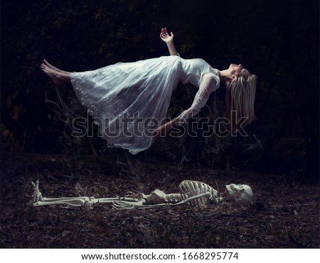 Levitation image of a woman rising from a skeleton on some dead leaves Royalty-Free Stock Photo #1668295774