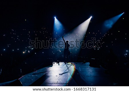 View from the stage stadium. Vocalist of a popular pop band on the background of the flashlights  of phones during a concert. Fans switch on lights on smart phones on tribunes. Crowd waving cellphones #1668317131