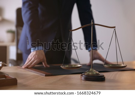 Male lawyer at table in office, focus on scales of justice #1668324679