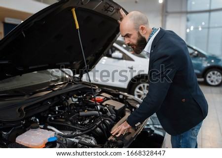 Man looking on transport engine in car dealership #1668328447