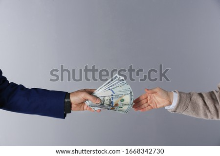Man giving bribe money to woman on grey background, closeup #1668342730