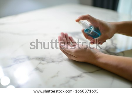 Image of a hand of a man with a bottle of alcohol washing hands.Stop and staying safe from COVID-19 Royalty-Free Stock Photo #1668371695