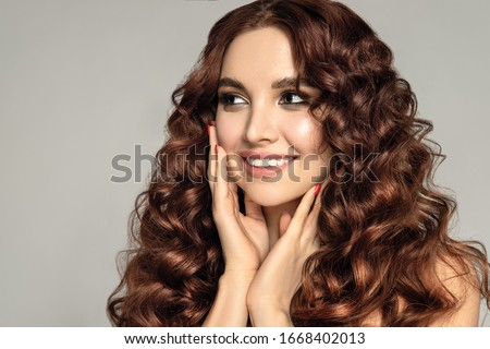 Fashion portrait of a beautiful young brunette with wavy hair and red nail #1668402013