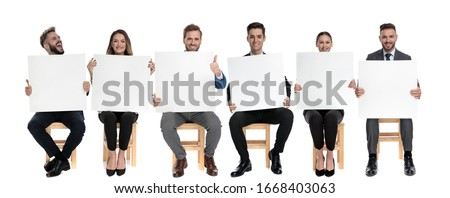 Team of 6 businessmen holding blank billboard while one of them is shouting while sitting on chairs on white studio background