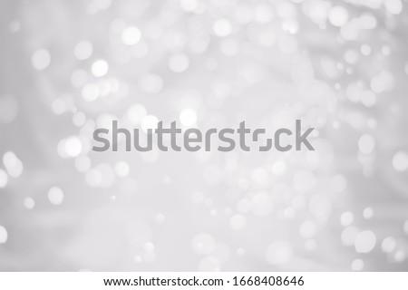 White glitter vintage lights background. White bokeh on background.