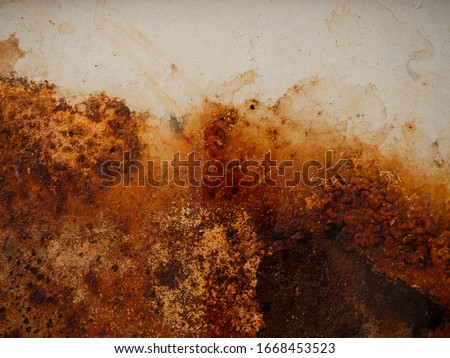 Brown and yellow wet rust and dirt on white enamel with smudges of water and drops. Rusted brown and white abstract texture. Corroded white metal background. Rusty white painted metal wall. #1668453523