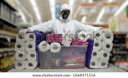 Man in a disposable face mask gloves and white suit while in panic shopping in a supermaket due to corona virus crisis #1668471556