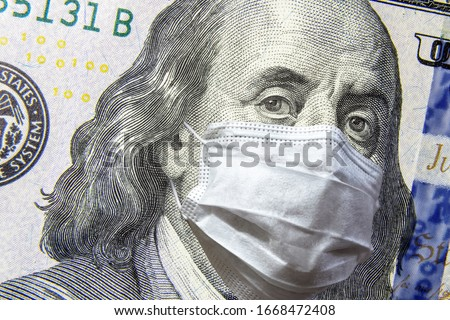 COVID-19 coronavirus in USA, 100 dollar money bill with face mask. COVID affects global stock market. World economy hit by corona virus outbreak. Financial crisis and coronavirus pandemic concept. #1668472408