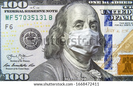 COVID-19 coronavirus in USA, 100 dollar money bill with face mask. Coronavirus affects global stock market. World economy hit by corona virus outbreak and pandemic fears. Crisis and finance concept. Royalty-Free Stock Photo #1668472411