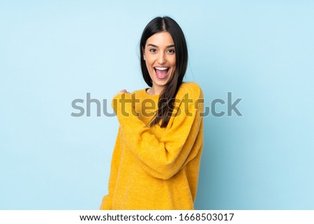 Young caucasian woman isolated on blue background celebrating a victory #1668503017