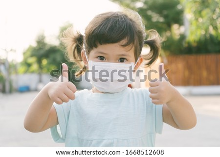 Little asian girl wearing mask for protect pm2.5 and show thumbs up gesture for good air outdoor.Air pollution pm2.5 and Coronavirus concept #1668512608