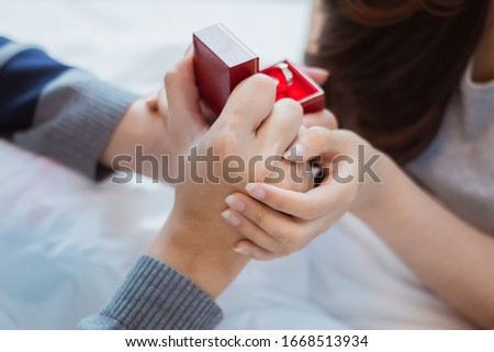 Attractive young Asian smile couple man offer wedding ring to happy and excited woman for marriage proposal in romantic moment. Lover bonding and relationship. Husband and wife in love photo concept.