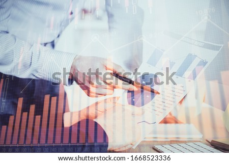 Financial trading graph double exposure with man desktop background. #1668523336