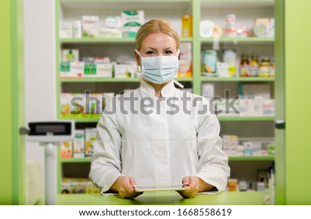 Pleasant professional young female pharmacist with surgical mask smiling  Royalty-Free Stock Photo #1668558619