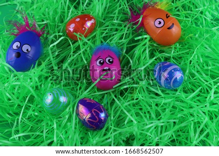 Easter decorations. This pictures has  Eggs with silly faces mixed in with some colorful eggs on top of Easter grass.