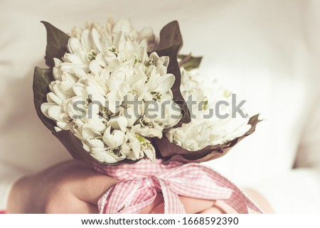 lilies of the valley bouquet in girl's hands. Small flowers beige toned. close up picture. first spring flowers concept.