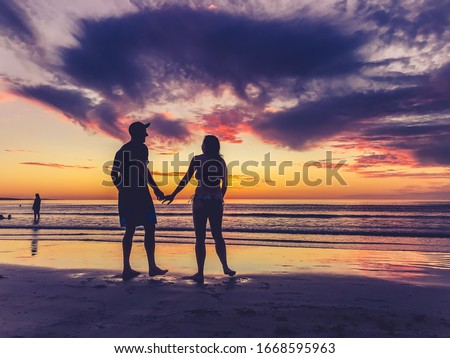 Couple in love holding hands feeling free during honeymoon at spectacular beach sunset. Man and woman silhouette celebrating love freedom and health. Romantic escapes holidays and wellness concept. #1668595963