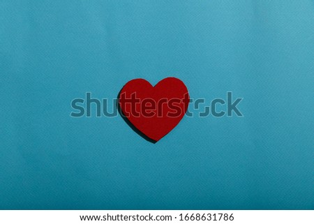 Medical background. On a blue background the figure of a red heart in the center. Abstract background with a red heart in the center of the frame. A lot of free space for text, horizontal, closeup.