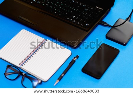 top view desktop formed by computer, black notebook, pen,phone,glasses, and external HDD with bright blue background. #1668649033