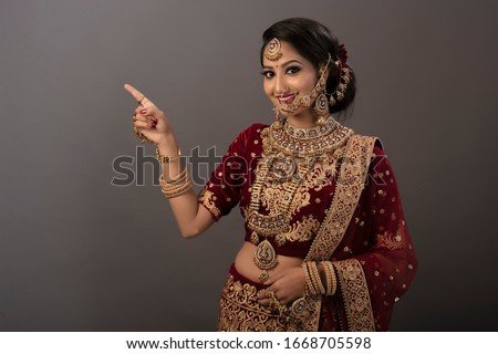 Indian woman with happy expressions and wearing the bridal wear and bridal jewelry #1668705598