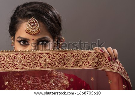 Indian woman with happy expressions and wearing the bridal wear and bridal jewelry #1668705610