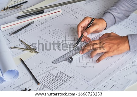 Architect engineer contractor design working drawing sketch plan blueprint and making architectural construction house building in architect studio.                              #1668723253