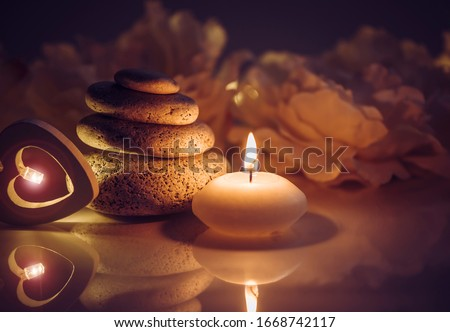 Flat round zen stones stacked in spa with candle flame and reflection in darkness, blurred flowers petals on background.